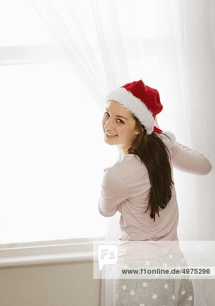 Frau zieht Vorhänge zur Seite  lacht