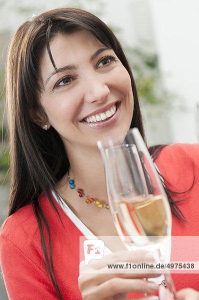 Lächelnde Frau trinkt Glas Wein
