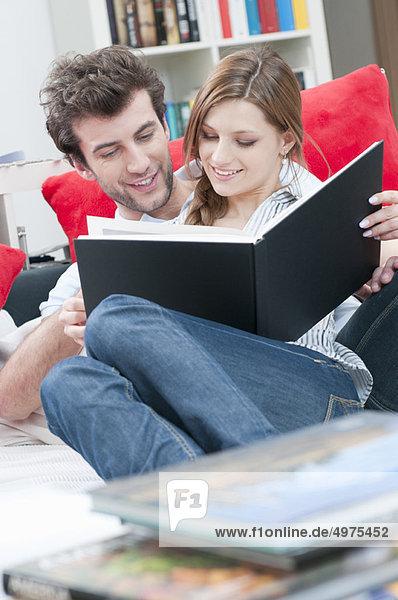 Paar liest zusammen ein Buch auf Sofa