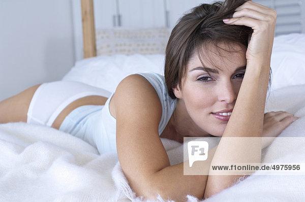 Frau lächelnd und auf dem Bett liegend