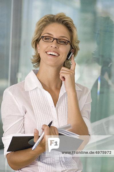 Geschäftsfrau lächelt am Telefon