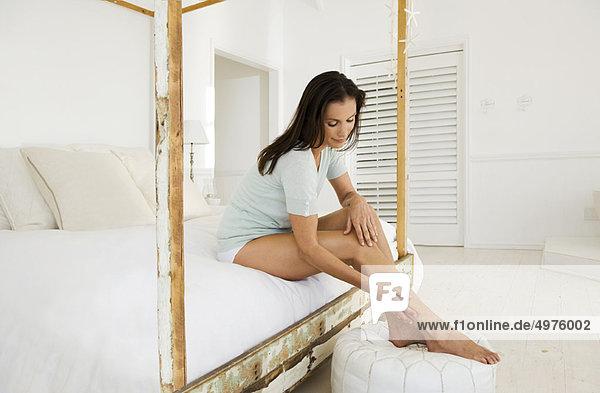 Frau streichelt ihre Beine