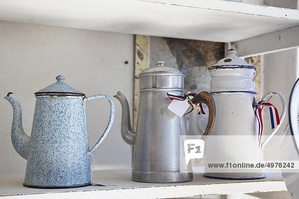 Alte emaile Kaffeekannen im Regal Alte emaile Kaffeekannen im Regal