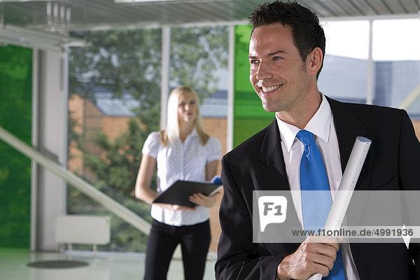 Lächelnder Geschäftsmann mit Frau im Hintergrund