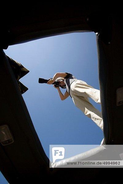 Photographer standing on safari vehicle - Lake Nakuru National Park  Kenya