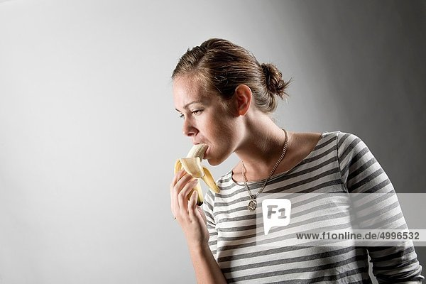 Junge Frau isst eine Banane