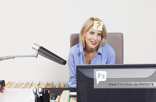 Eine Frau sitzt an einem Schreibtisch mit einem Klebezettel auf der Stirn.