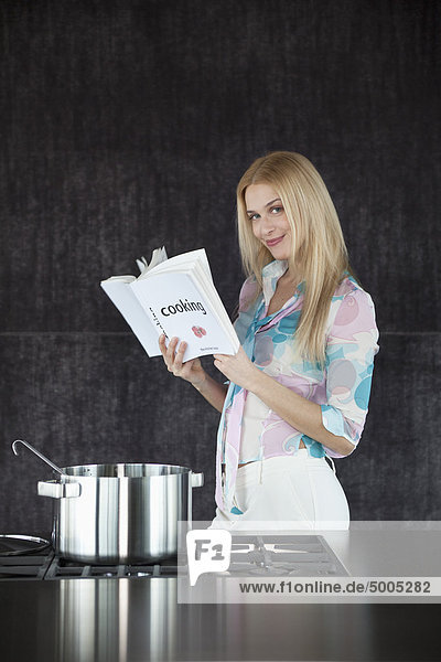 Woman cooking  content holding a cookery book.