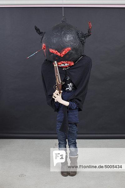 Kind mit Halloween-Outfit und Pistole.
