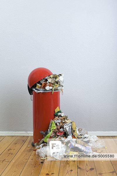 Eine überquellende Mülltonne mit verrottenden Lebensmitteln und Wertstoffen.