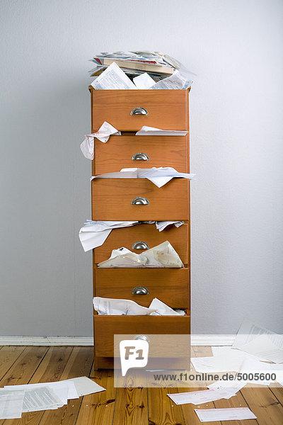 Ein Schrank gefüllt mit überfließenden Papieren.