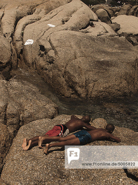 Two men sunbathing on a large rock by a stream
