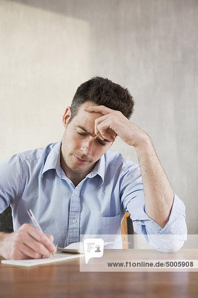 Ein Mann  der die Stirn runzelt  während er einen Scheck schreibt.