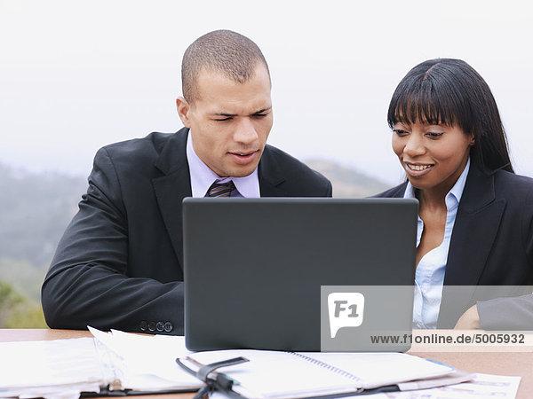 Ein Geschäftsmann und eine Geschäftsfrau  die zusammen einen Laptop benutzen.