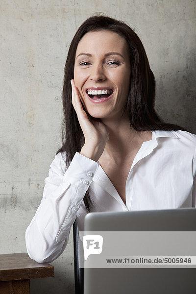 Eine Geschäftsfrau mit einem Laptop  die lacht.
