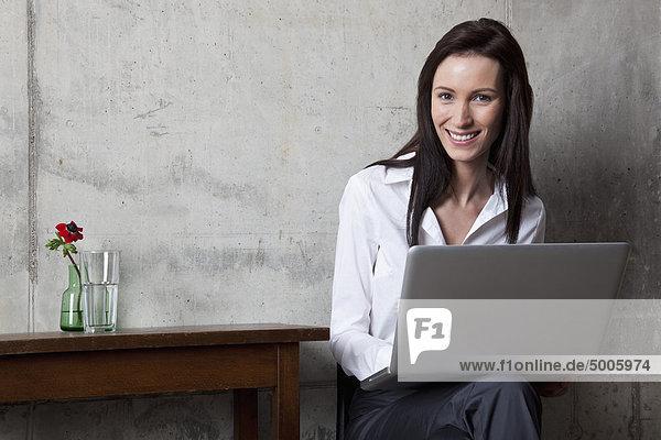 Eine Geschäftsfrau mit einem Laptop  der die Kamera anlächelt.