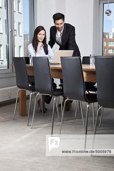 Ein Geschäftsmann und eine Geschäftsfrau  die sich in einem Vorstandszimmer treffen.