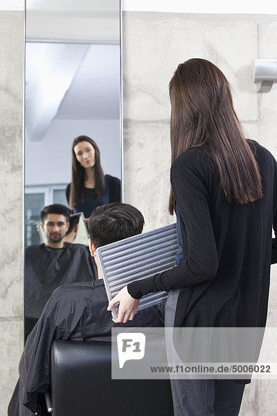 Ein Friseur hält einen Spiegel für einen Kunden  Rückansicht
