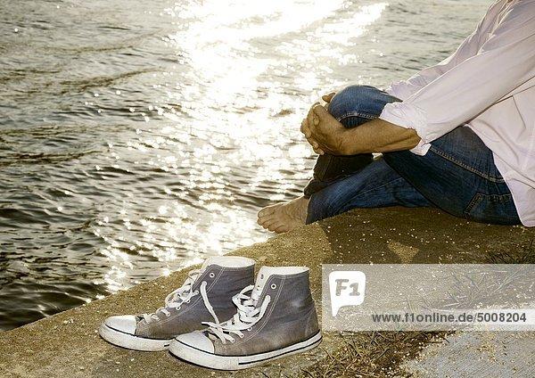 Man sitzt am Ufer Man sitzt am Ufer