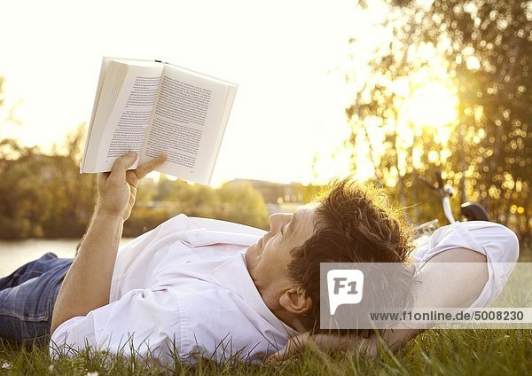 Mann liest ein Buch auf einer Wiese