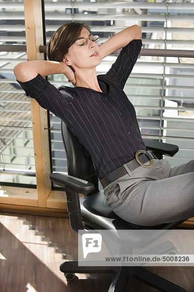 Brünette Frau auf Bürostuhl entspannt