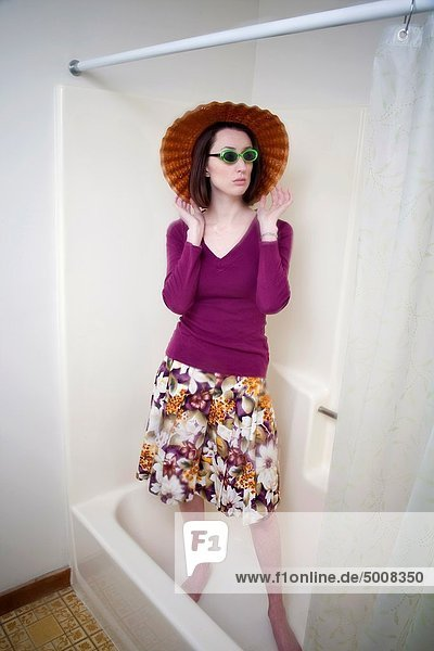 Young woman  wearing sunglasses  a hat  and all her clothes  standing in the bathtub