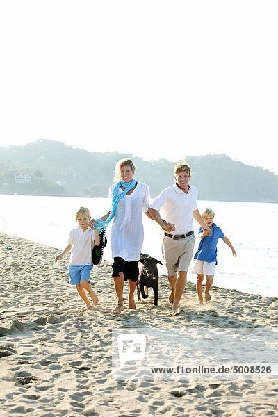 family walking on beach with dogs