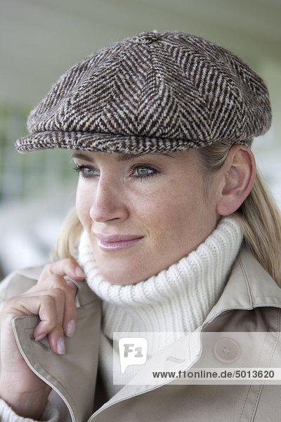 Blonde Frau mit Mütze und Mantel