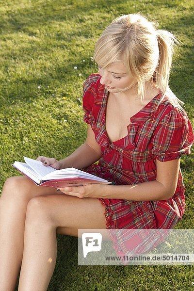 Junge blonde Frau liest ein Buch im Gras