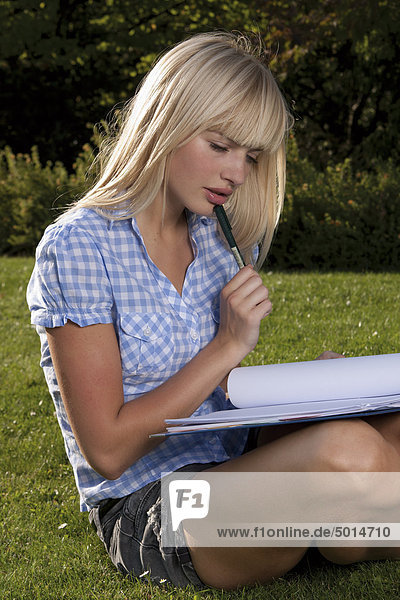 Young blond woman sitting in grass with file folder
