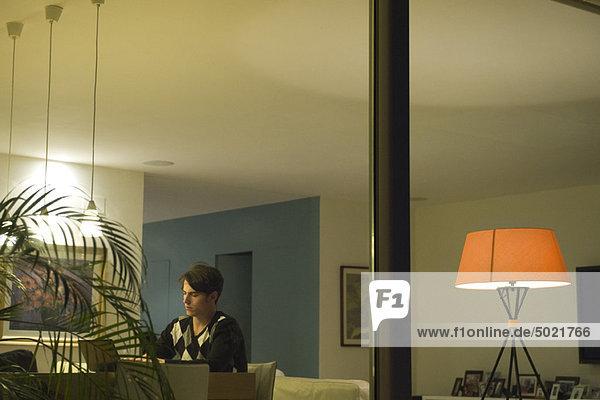 Mann mit Laptop im Wohnzimmer  durchs Fenster gesehen