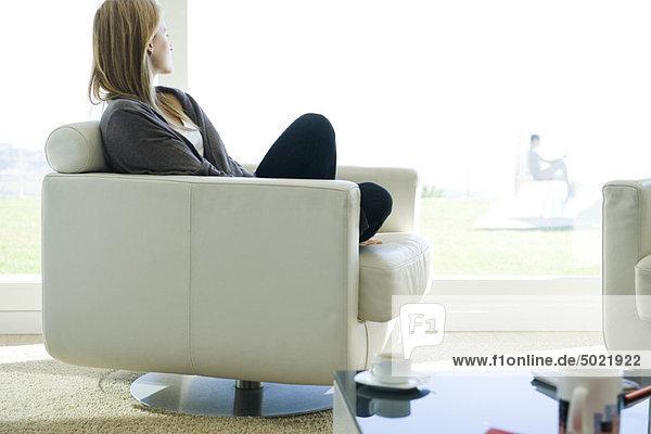 Frau entspannt sich im Sessel  blickt aus dem Fenster
