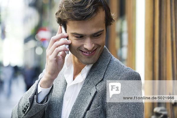 Ein Mann  der draußen am Handy telefoniert.