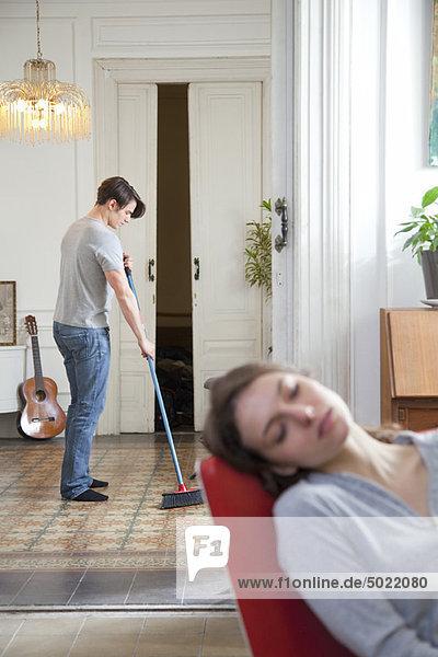 Mann schwingt den Boden zu Hause  Frau schläft im Vordergrund