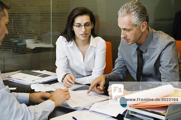 Kunden besprechen den Papierkram mit dem Geschäftsmann