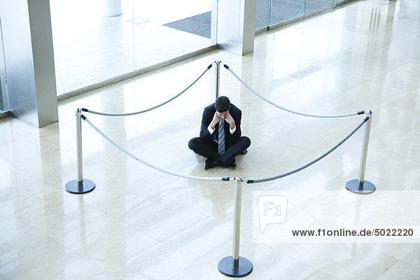 Geschäftsmann sitzend auf dem Boden im abgetrennten Bereich in der Lobby