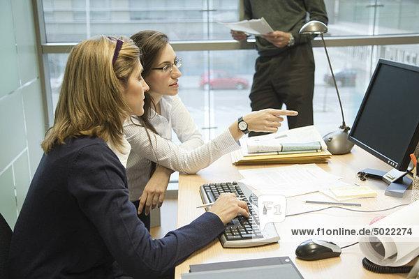 Kollegen  die gemeinsam am Desktop-Computer arbeiten