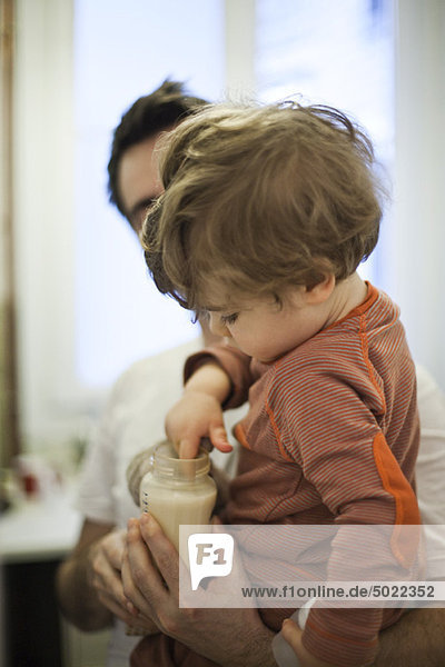 Toddler boy in father's arms  testing temperature of milk in baby bottle