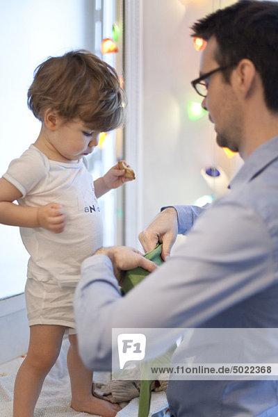 Vater hilft Kleinkind Sohn anziehen