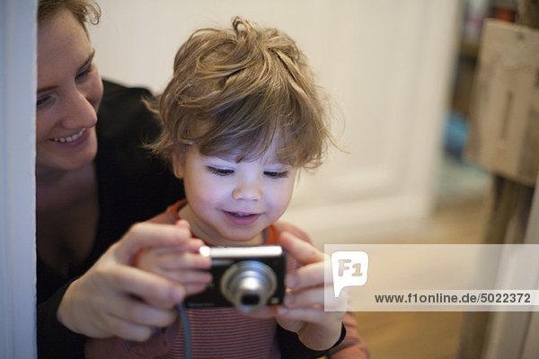 Mutter und Kleinkind Sohn schauen gemeinsam auf die Digitalkamera