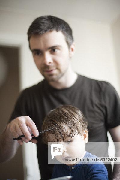 Vater schneidet das Haar des Kleinkindes.