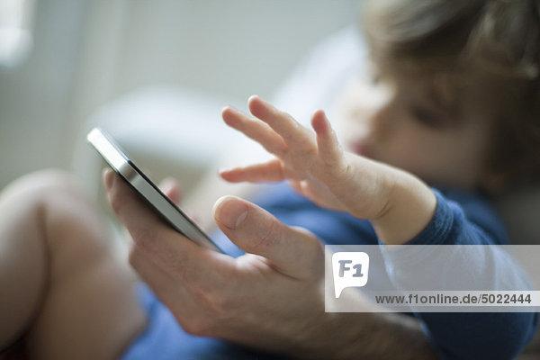 Kleinkind berührt Vaters Handy