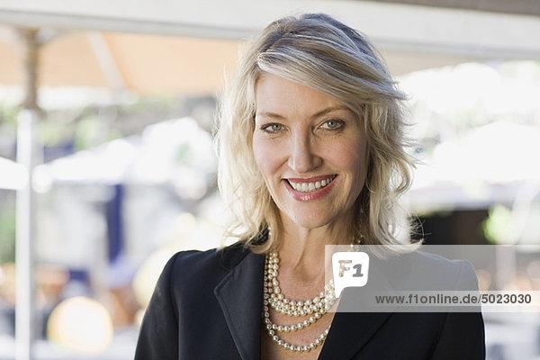 Smiling businesswoman wearing pearls