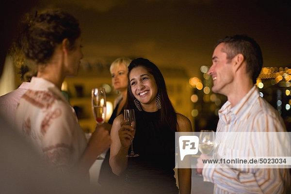 Leute  die nachts auf der Terrasse Wein trinken.