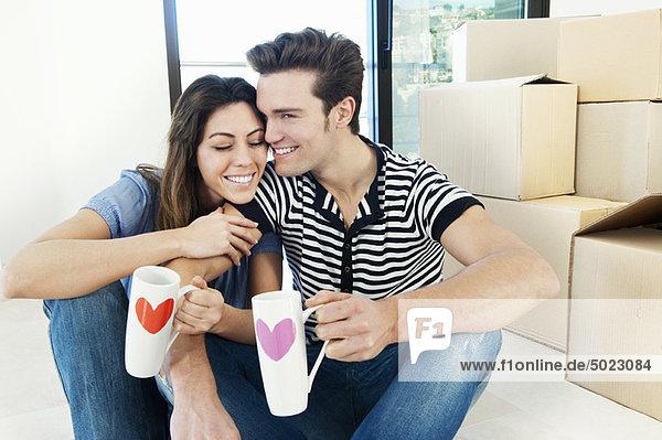 Paar trinkt Kaffee im neuen Zuhause