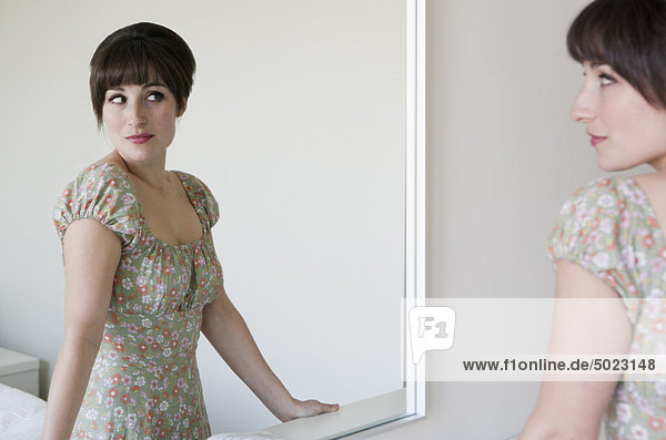 Frau bewundert sich im Spiegel
