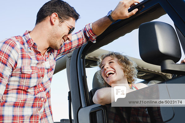 Lächelndes Paar spricht in der Nähe des Jeeps