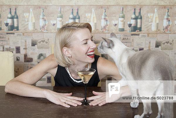 Frau trinkt Martini mit Katze