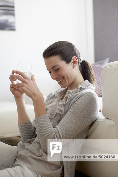 Lächelnde Frau am Sofa sitzend