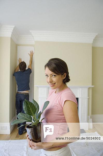 Frau tragen Pflanze Eigentumswohnung neues Zuhause